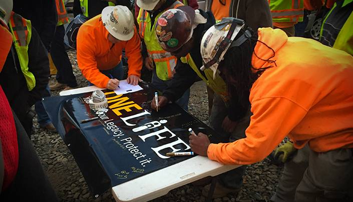 """This picture depicts the signing of the """"We Work Safe For"""" banner, where all onsite personnel sign who they are working safe for. This significant banner then is hung through the duration of the project to remind everyone what's really at stake for themselves and their fellow workers. Credit: Keith Smith, Choate Construction Company"""